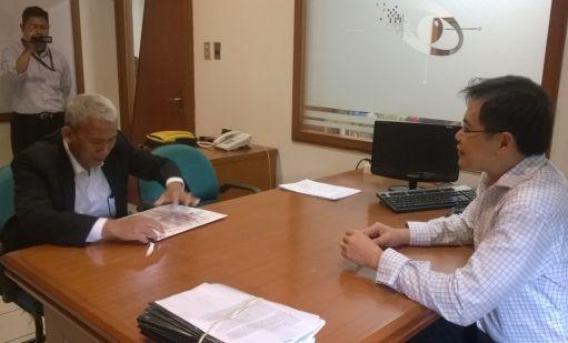 Pengawas tes dari BINUS, Dr. Besar, sedang membuka segel soal yang dikirim oleh the College of Law, Australia.
